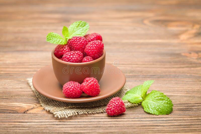 与绿色薄荷叶的新鲜的成熟莓在棕色茶杯在麻袋布和木背景 图库摄影
