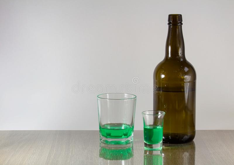 与绿色酒精和瓶的两块玻璃在白色背景 免版税库存图片