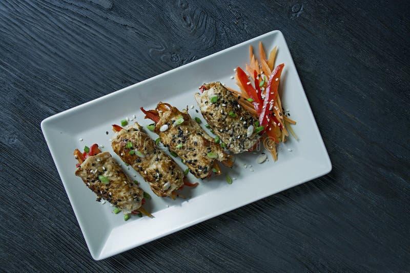 与绿色,红萝卜切片,在一块轻的长方形板材的甜椒的自创鸡胸脯卷 亚洲烹调的概念 图库摄影