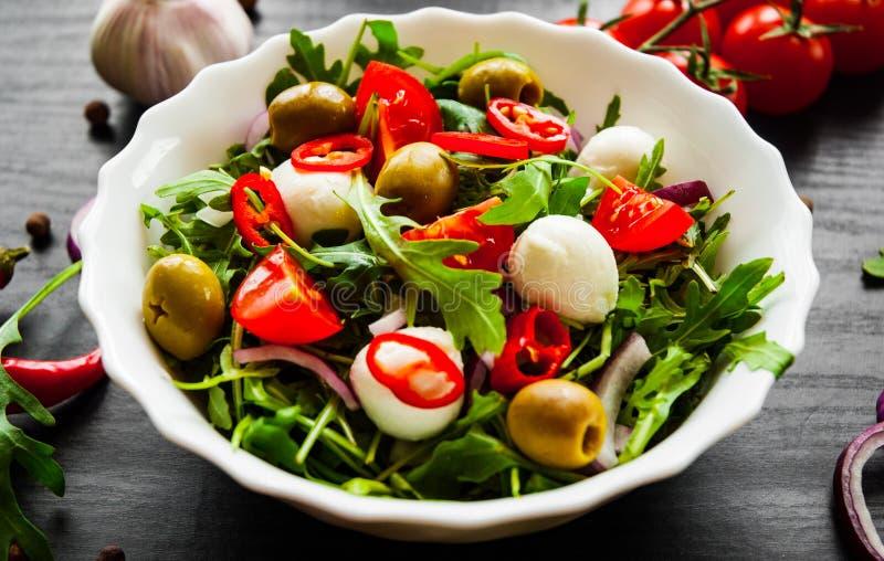 与绿色rucola,乳酪,橄榄,蕃茄,葱,在白色碗的胡椒的沙拉在黑暗的木背景 免版税库存照片