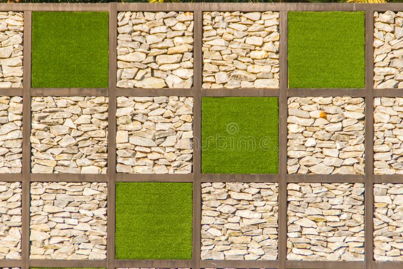 与绿草框架的抽象河小卵石石墙背景 铺石渣墙壁backgr的背景和绿草正方形形状 库存图片