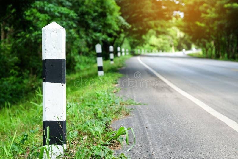 与绿草路旁,树路的黑白里程碑 免版税库存图片