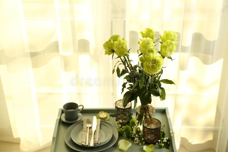 与绿蔷薇花束的表设置在窗口附近的 免版税库存照片