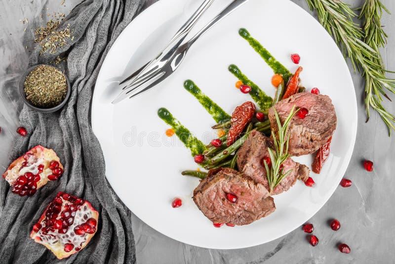 与绿豆、石榴和调味汁的水多的中等牛肉里脊肉牛排可爱的孩子在灰色背景的板材 热的肉盘,上面 免版税库存照片