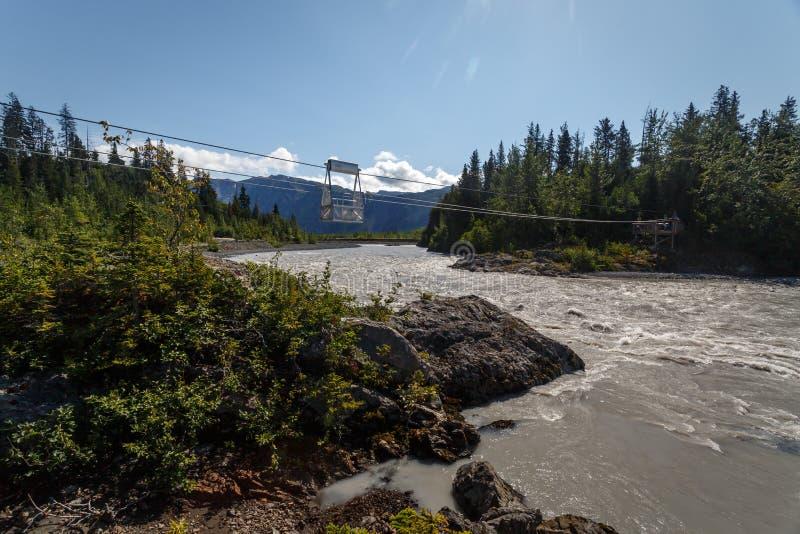 与缆绳滑轮推车的河流桥渡在阿拉斯加原野 库存图片