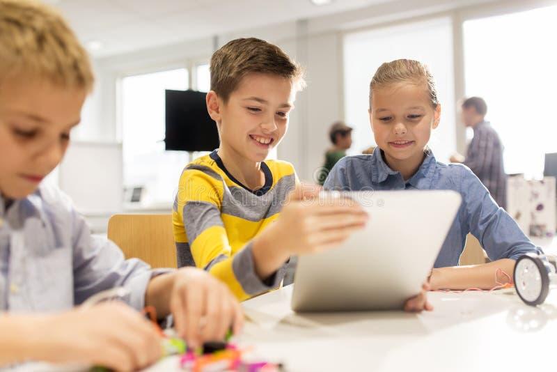 与编程在机器人学学校的片剂个人计算机的孩子 免版税库存照片