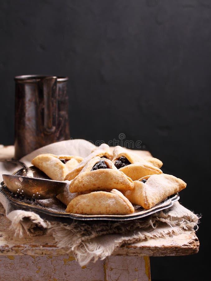 与罂粟种子和risins的Hamantaschen曲奇饼和在板材的糖粉 免版税库存照片