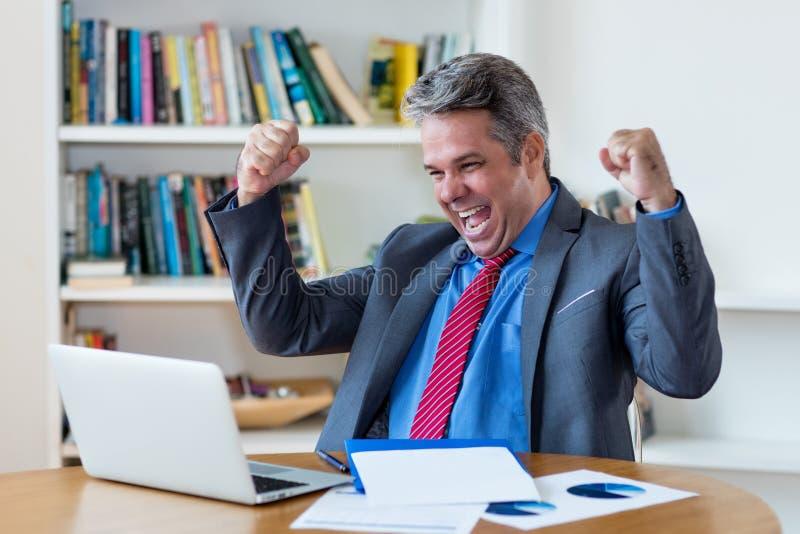 与网上事务的欢呼的成熟商人赚钱 免版税库存照片