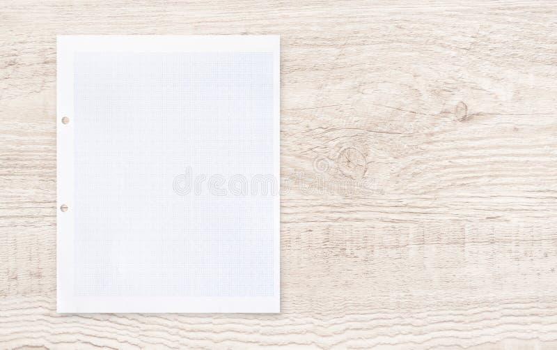 与网格线样式的白皮书板料在木头 图库摄影