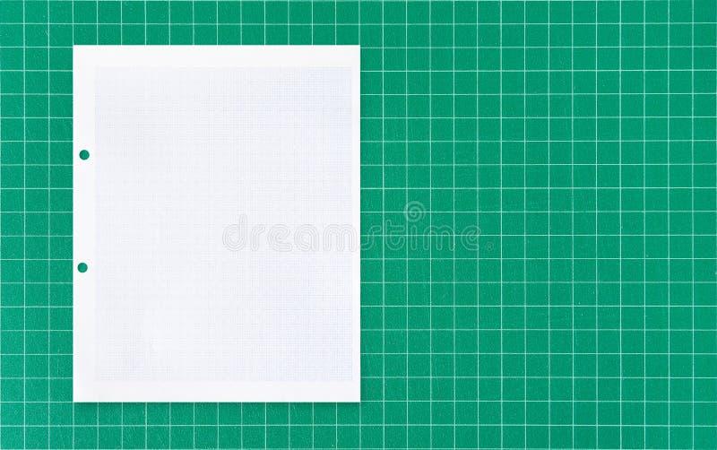 与网格线样式的白皮书板料在绿色席子背景 免版税库存图片