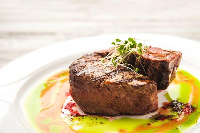 与罕见的程度的烤肉烹调,中等,很好做 关闭牛肉在调味汁和新芽的猪肉牛排 库存照片
