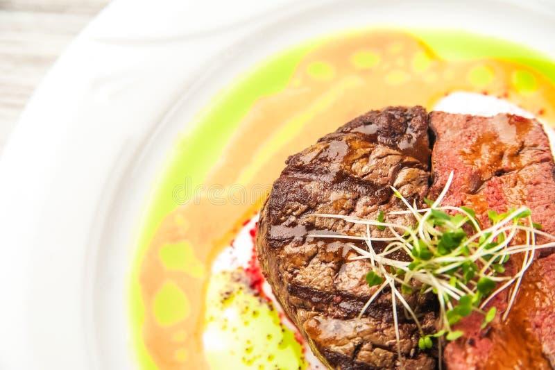 与罕见的程度的烤肉烹调,中等,很好做 关闭牛肉在调味汁和新芽的猪肉牛排 免版税库存图片