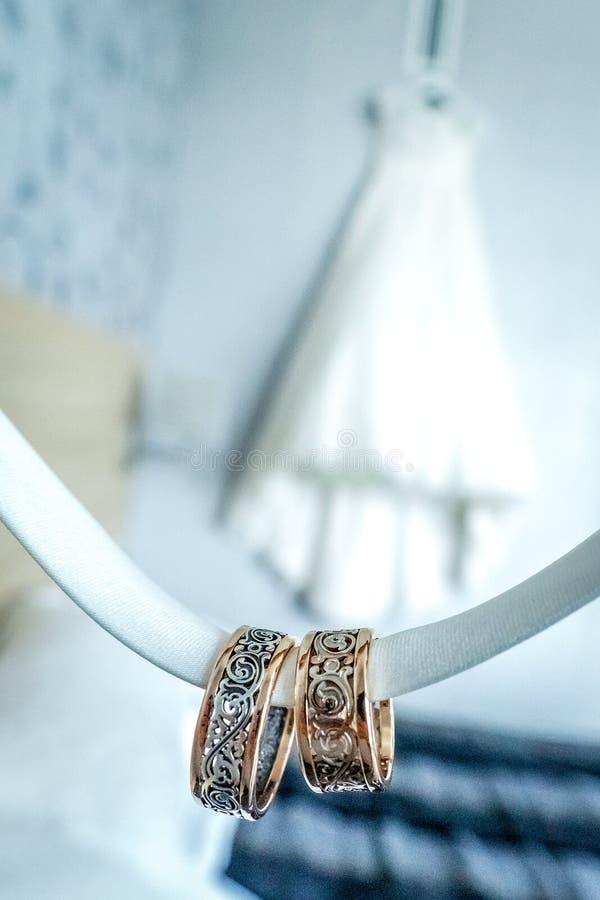 与罕见的设计的两个圆环在婚纱前面 库存图片