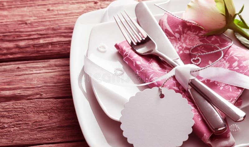 与罗斯和空白的标记的浪漫餐位餐具 图库摄影