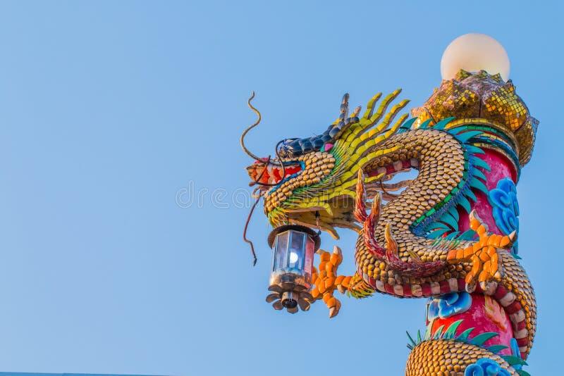 与羊羔的中国龙雕象在杆 图库摄影