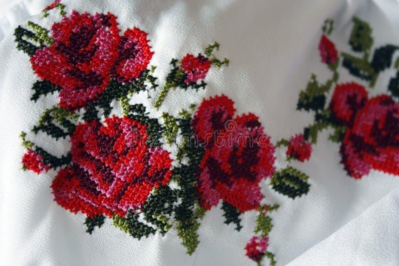 与美丽的五颜六色的英国兰开斯特家族族徽和绿色叶子,特写镜头的刺绣 十字绣纹理,民间服装 库存图片