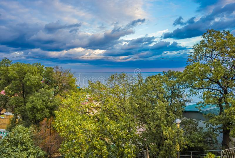 与美丽的多云天空、海和豪华的绿色树的风景在夏天 免版税库存图片