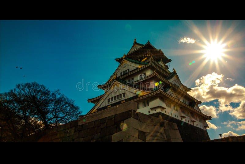 与美丽的太阳的大阪城堡 库存照片