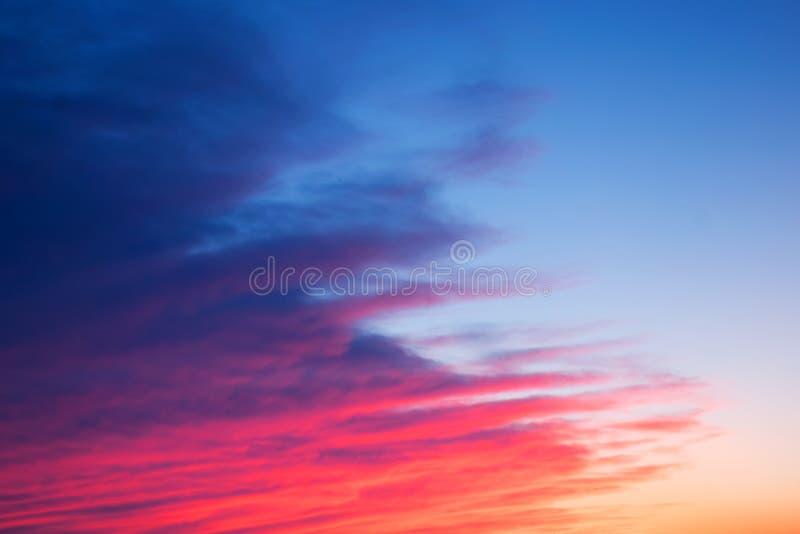 与美丽的对角云彩的红色,桃红色和蓝色明亮的日落 免版税库存照片