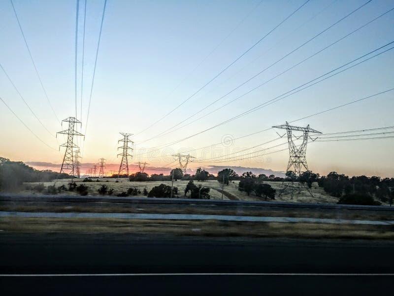 与美丽的小山和输电线的日出 库存图片