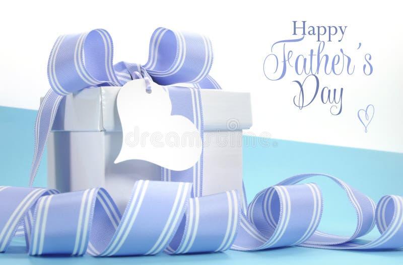 与美丽的条纹丝带的蓝色父亲节礼物和心脏塑造礼物标记 免版税库存图片
