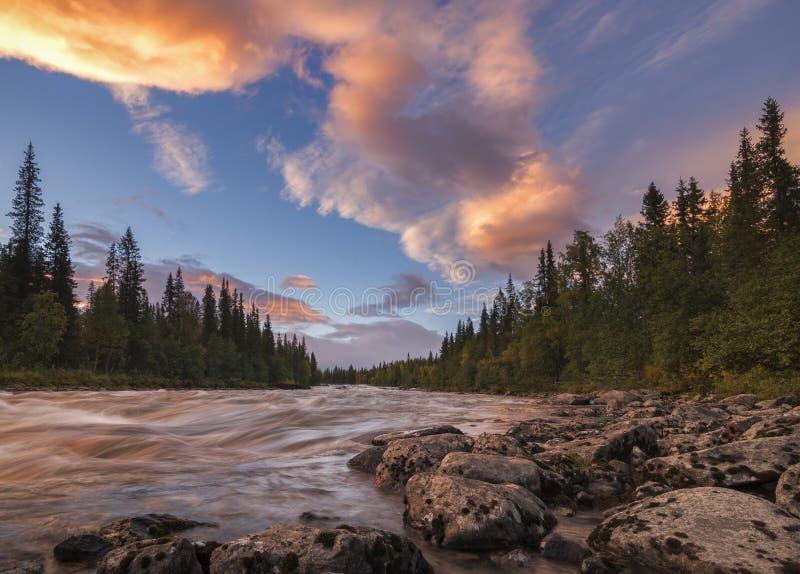 与美丽的橙色云彩的平静和镇静河日落,瑞典 库存照片
