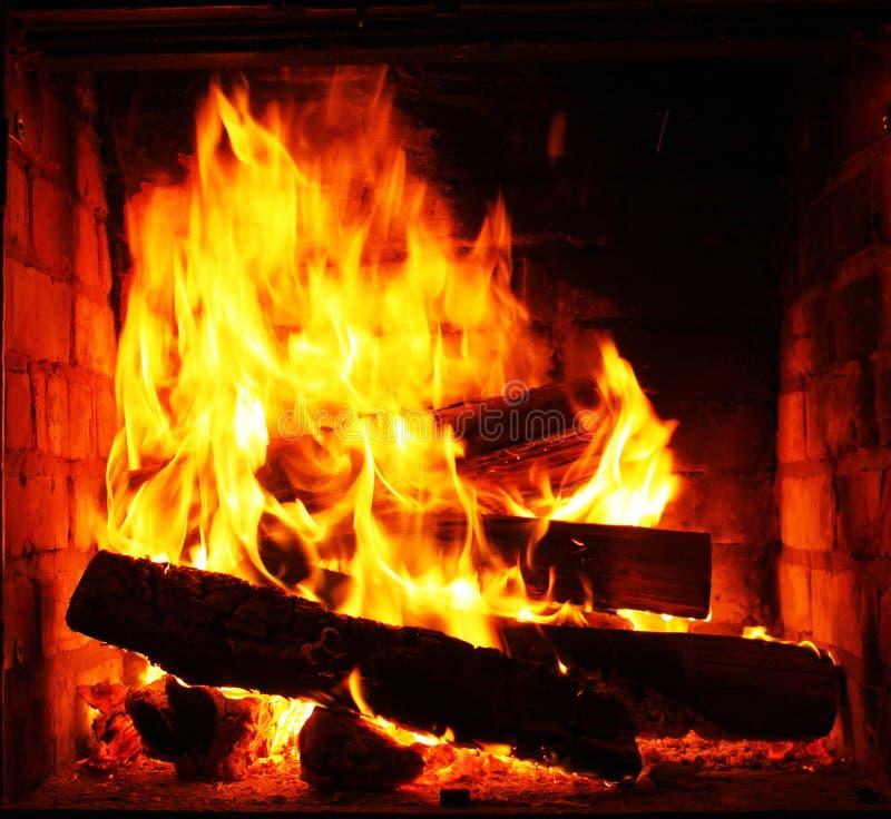 与美丽的橙色火和柴火特写镜头的家庭壁炉 免版税库存照片