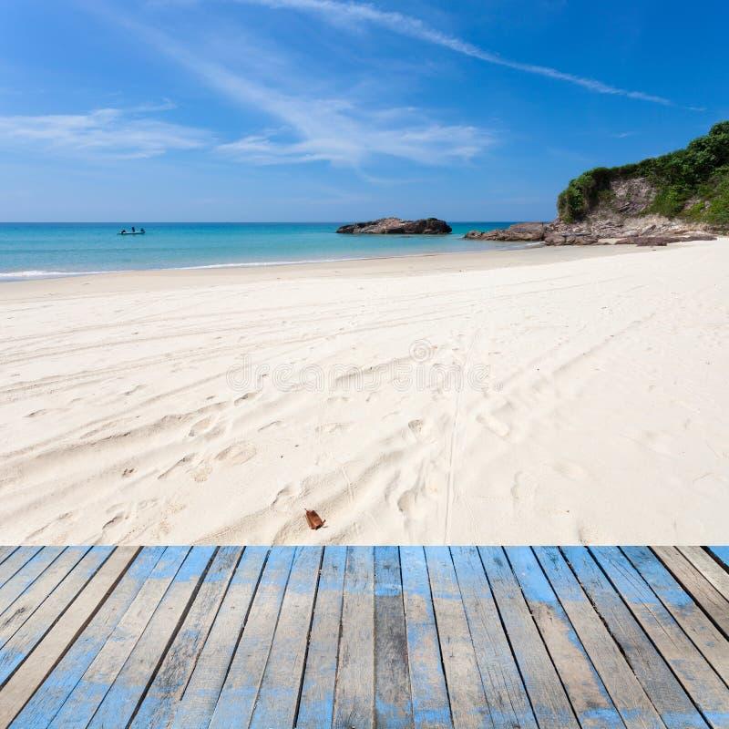 与美丽的沙子,热带海滩,蓝天场面的木地板 库存照片