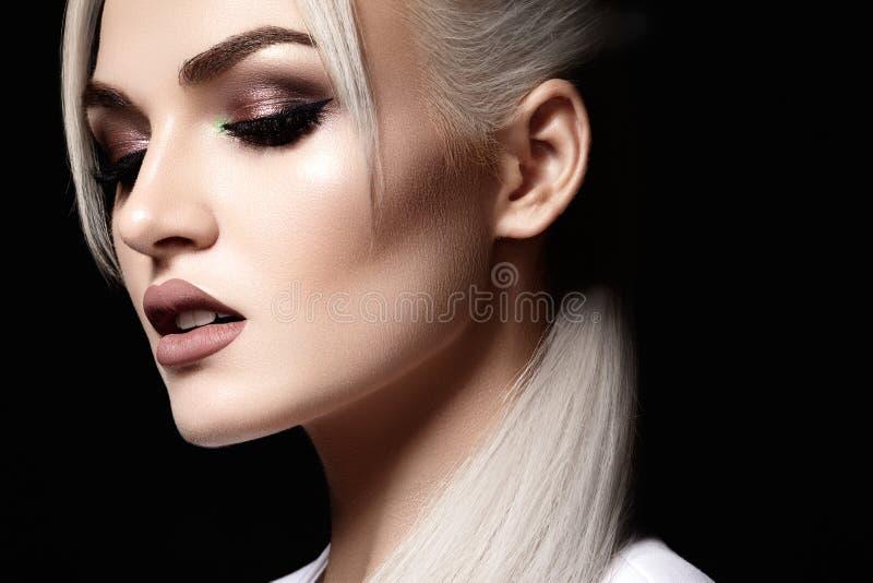 与美丽的白肤金发的妇女的特写镜头 时尚构成,干净的发光的皮肤 构成和化妆用品 在式样面孔的秀丽样式 库存照片