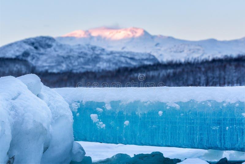 与美丽的蓝色冰的冬天风景在前景 库存图片