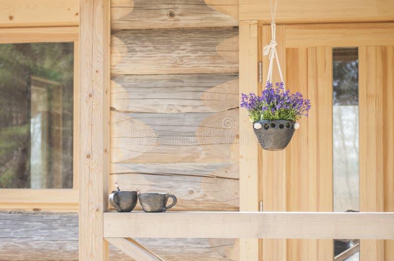 与美丽的风铃草和两个咖啡杯的夏天早晨心情垂悬的大农场主独特的手工制造黑瓦器 免版税库存图片