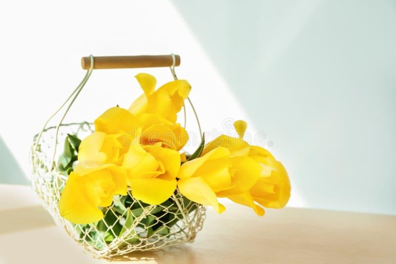 与美丽的黄色郁金香的篮子在户内桌上 库存照片