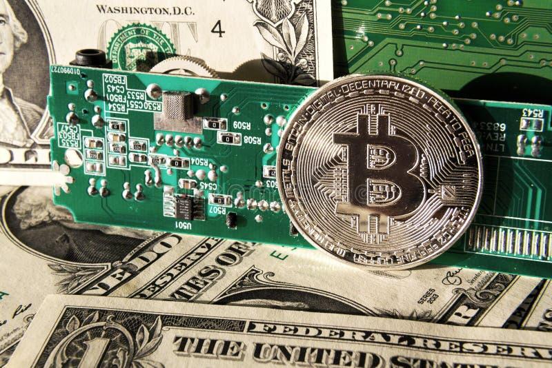 与美元和计算机主板,cryptocurrency采矿和投资的银色bitcoin硬币 免版税库存照片