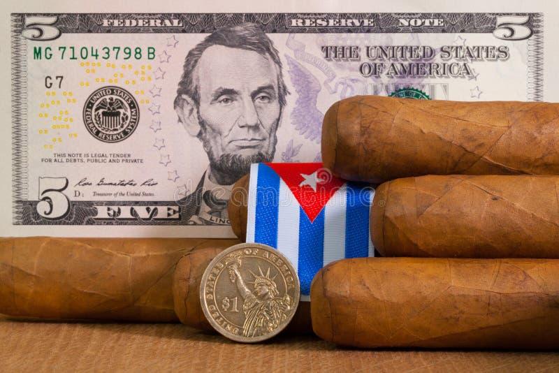 与美元钞票和硬币的豪华古巴雪茄 免版税库存照片