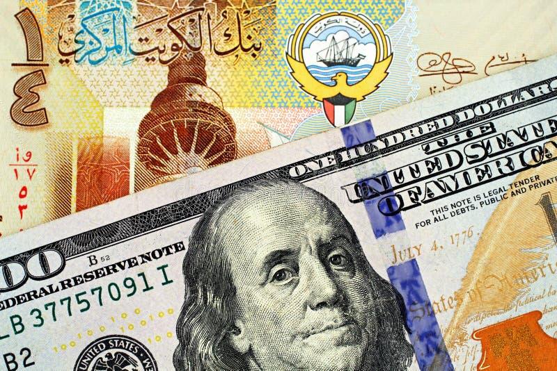 与美国一百元钞票关闭的一五颜六色的科威特四分之一丁那 免版税库存照片