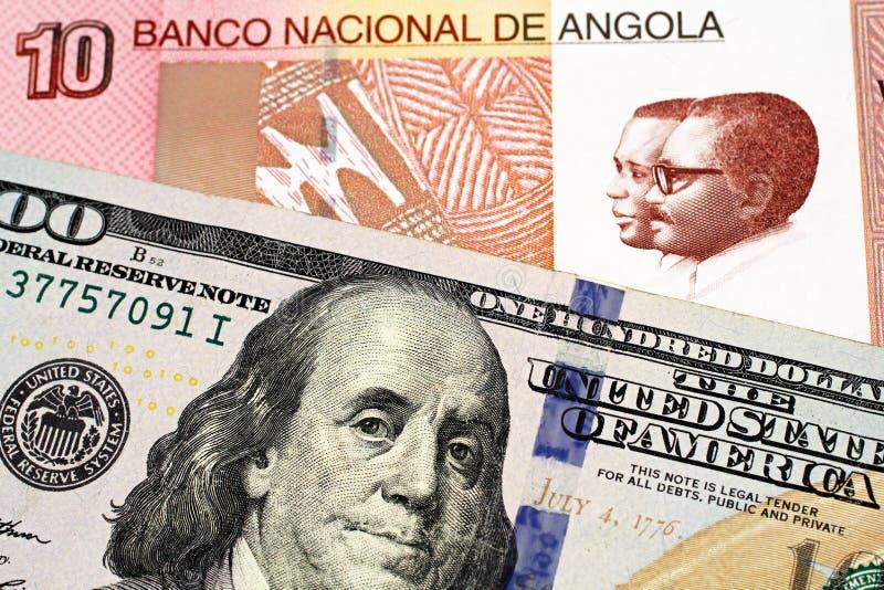 与美国一百元钞票的一张安哥拉宽扎钞票 图库摄影