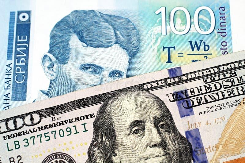 与美国一百元钞票的一张蓝色一百张塞尔维亚丁那钞票 免版税库存图片