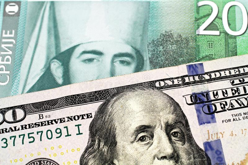 与美国一百元钞票的二十塞尔维亚丁那钞票 免版税库存照片