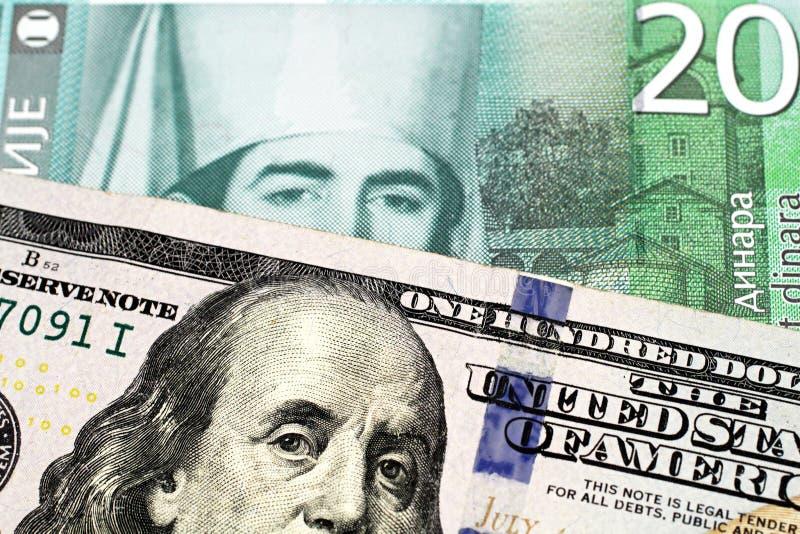 与美国一百元钞票的二十塞尔维亚丁那钞票 库存照片