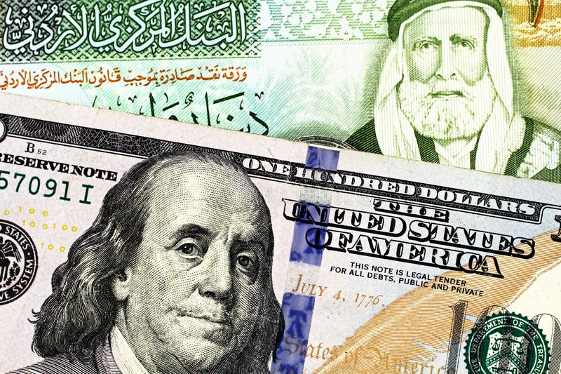与美国一百元钞票的约旦一丁那钞票 库存图片