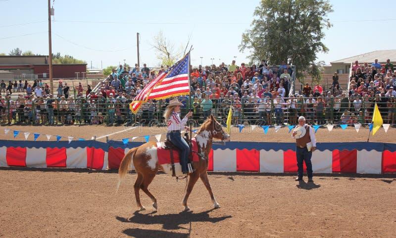 与美国国旗的女牛仔骑马 免版税库存照片