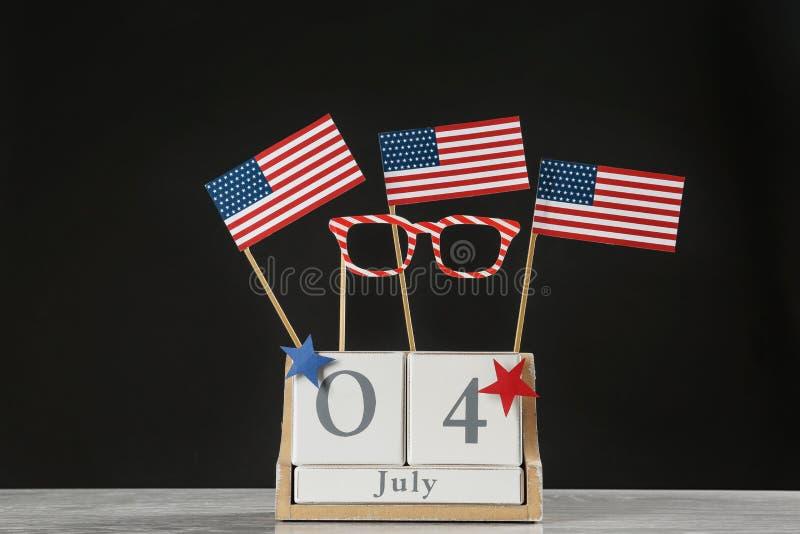 与美国旗子和纸玻璃的木日历在反对黑背景的桌上 图库摄影