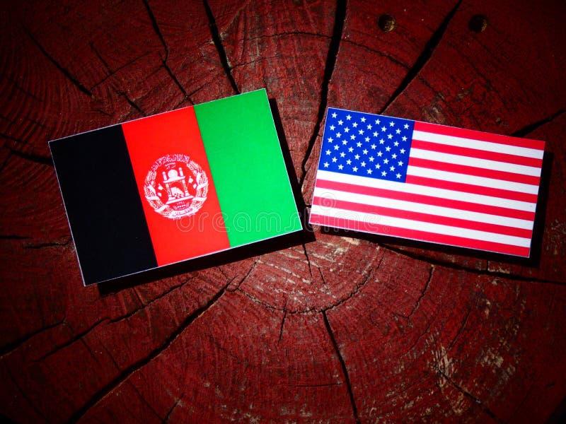与美国旗子的阿富汗旗子在树桩 库存图片