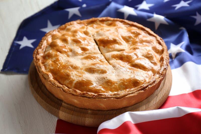 与美国的国旗的鲜美自创苹果饼在白色木桌上的 免版税库存图片