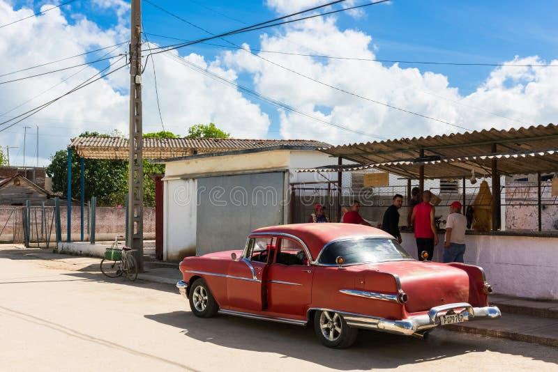 与美国红色克莱斯勒经典汽车的街道生活视图在圣克拉拉古巴- Serie古巴报告文学的一家街道商店前 免版税库存照片