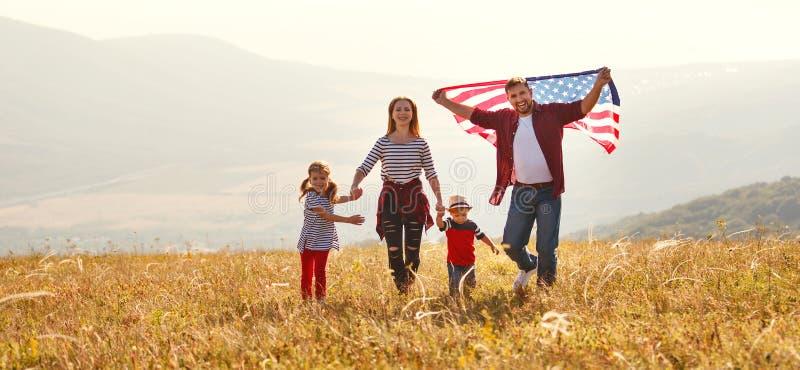 与美国美国的旗子的愉快的家庭日落的户外 免版税库存照片