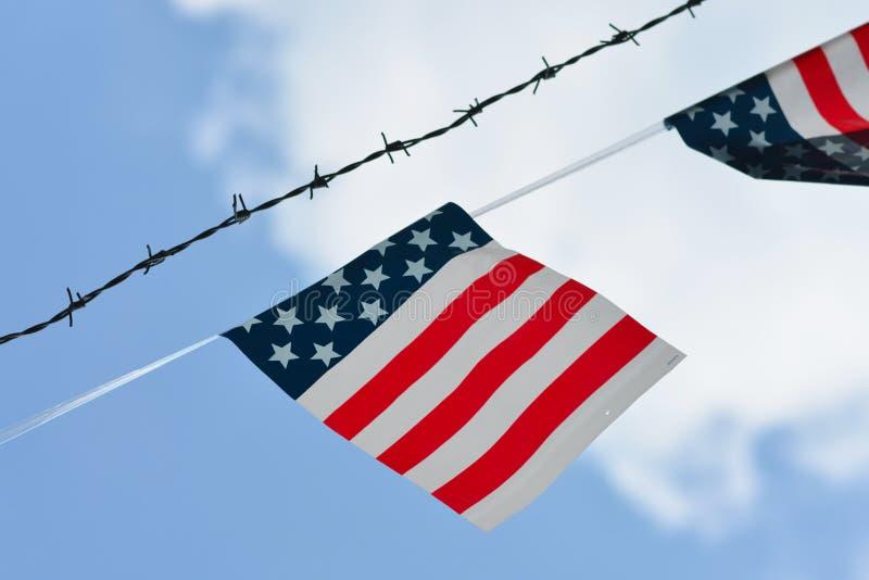 与美国颜色的被简化的旗子与红色条纹和白色星在垂悬在铁丝网篱芭旁边的蓝色背景在bl 免版税图库摄影