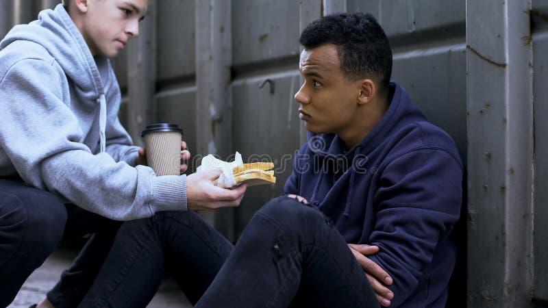 与美国黑人的朋友,在坚硬情况的支持的少年分享的午餐 库存图片