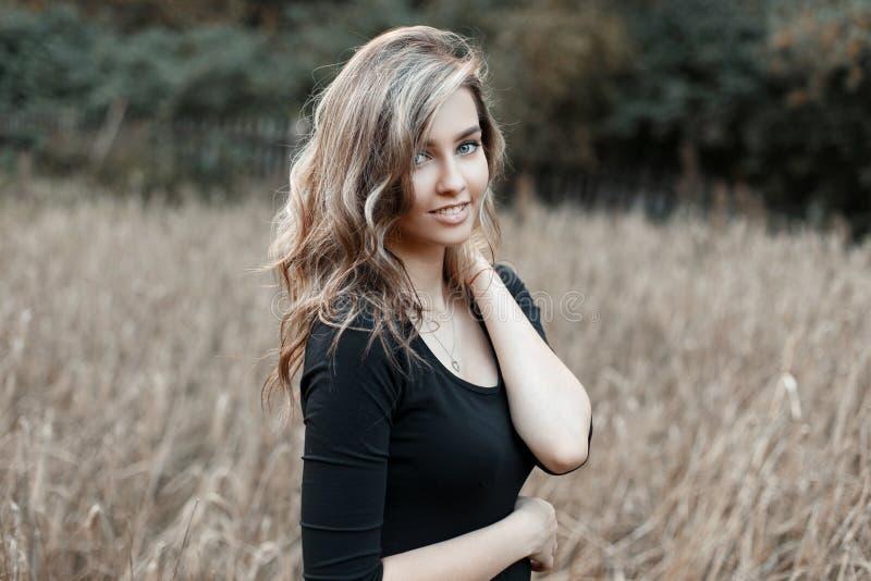 与美好的微笑的愉快的快乐的时髦的现代年轻女人模型在摆在麦地的时兴的黑T恤杉 免版税库存照片