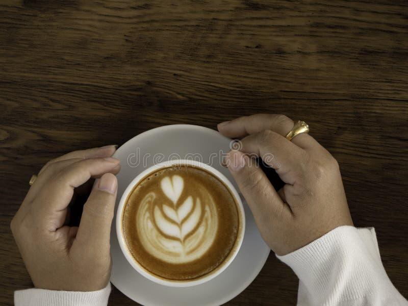 与美好的拿铁艺术的咖啡拿铁在手边 库存图片